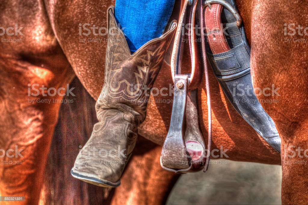 Cowgirl in boots on her horse stock photo