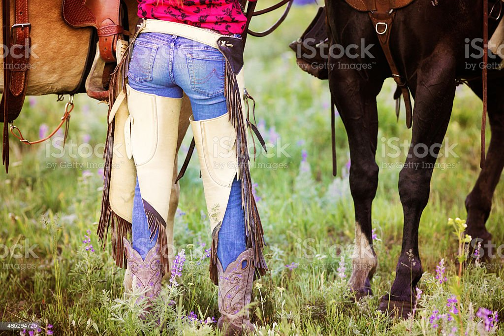 Cowgirl jeans and chaps rear view stock photo