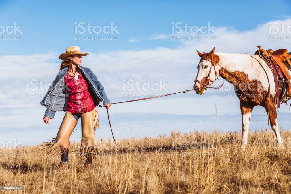 Cowgirl Leading Her Horse By The Reins stock photo