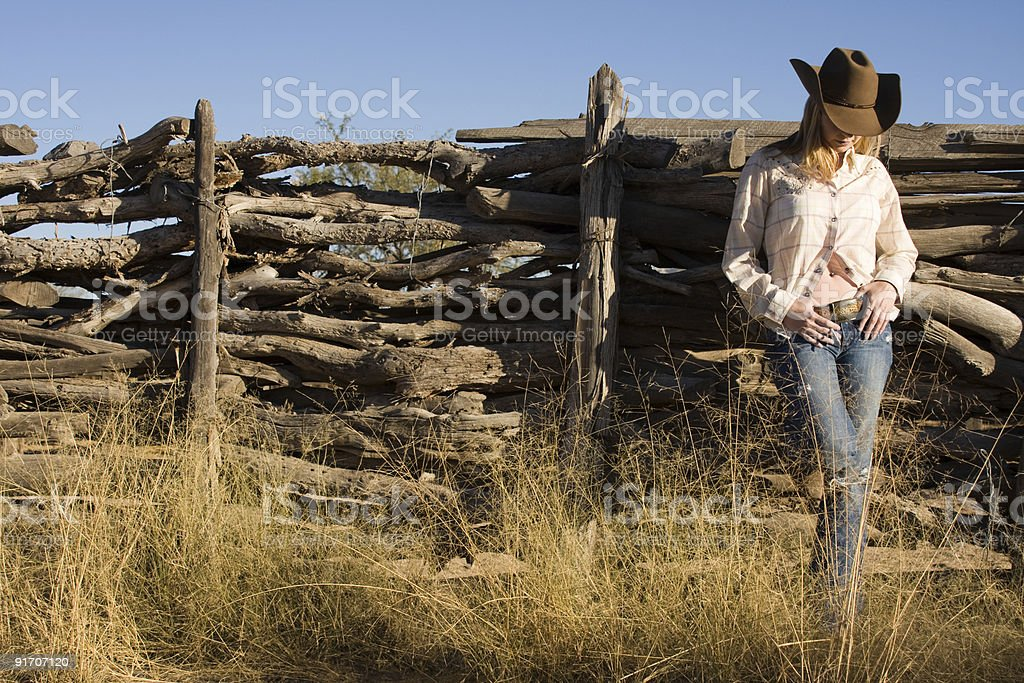 Cowgirl leaning on the fence royalty-free stock photo