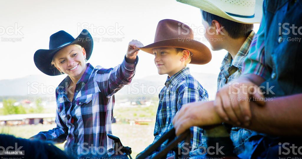 Cowgirl mother replacing son's cowboy hat while horse riding stock photo