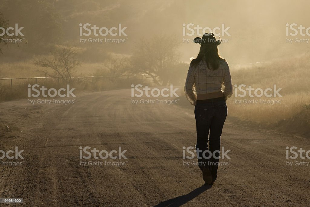 Cowgirl on a dusty road stock photo