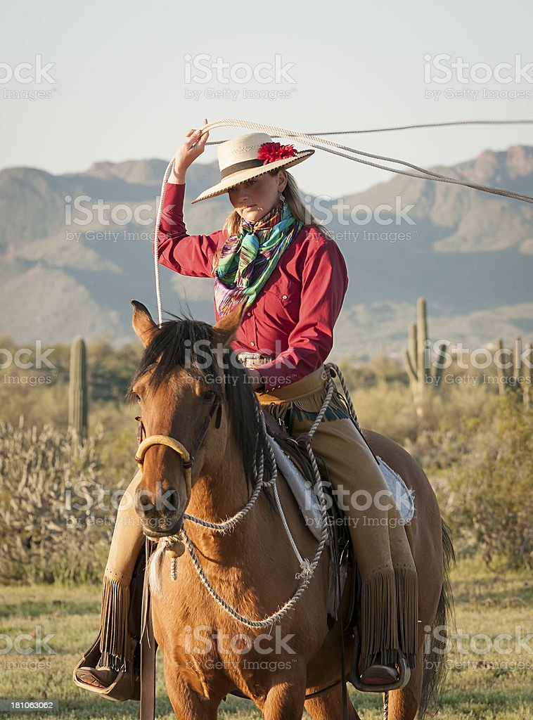 Cowgirl on horse throwing a lasso royalty-free stock photo