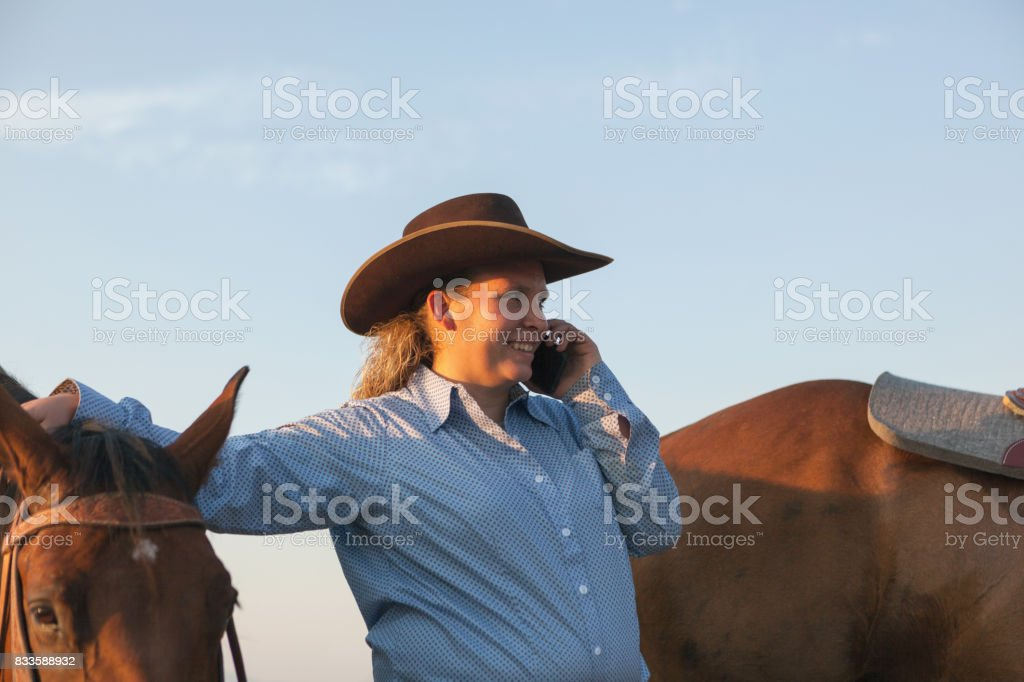 cowgirl on the cellphone stock photo