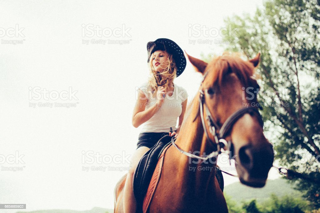 Cowgirl riding a horse stock photo