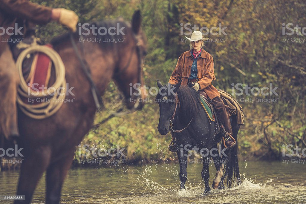 Cowgirl riding across a river stock photo