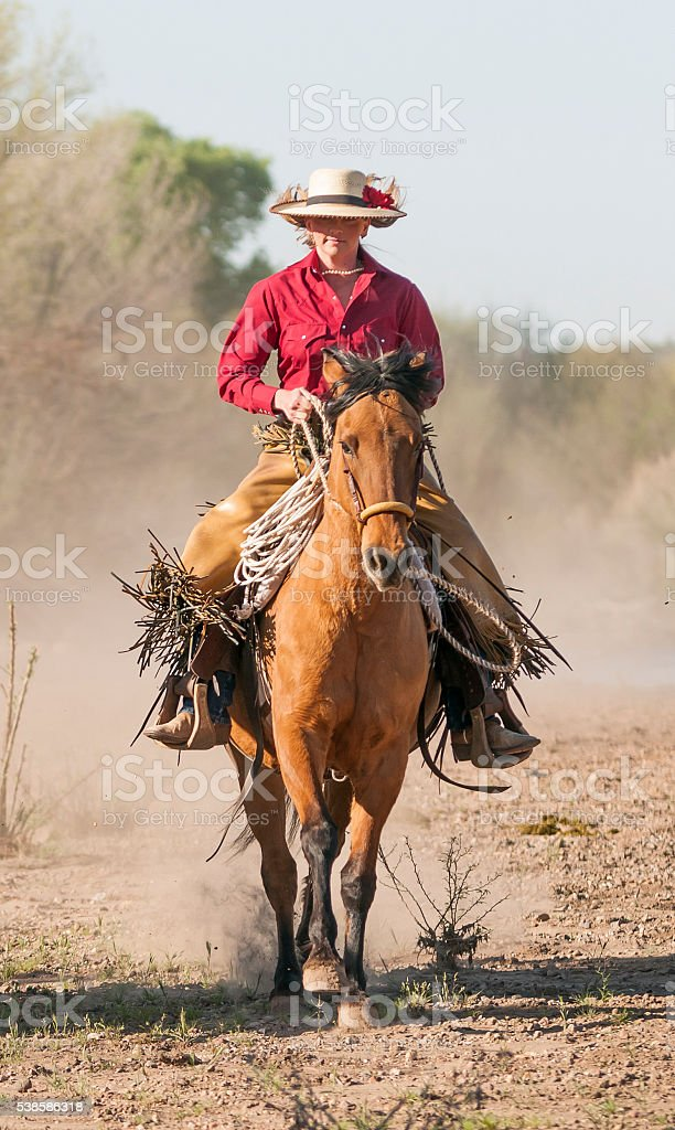 Cowgirl riding horse straight stock photo