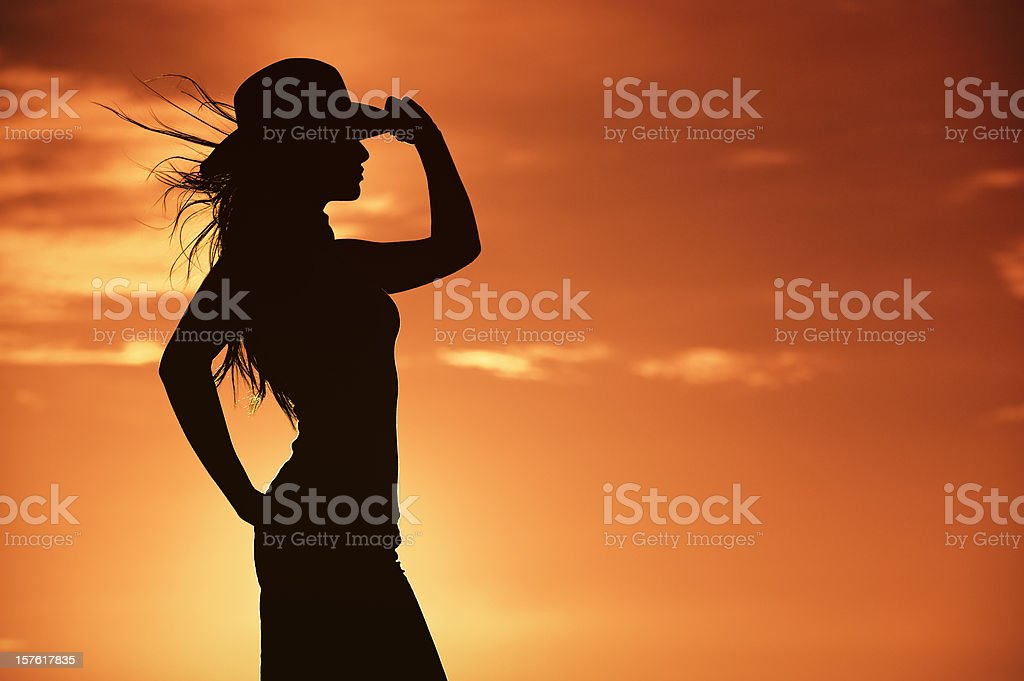 Cowgirl Silhouette In A Hot Orange Western Sky stock photo