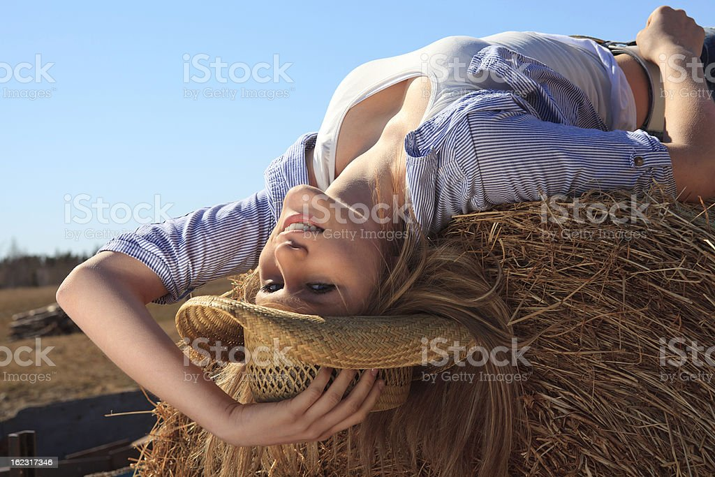 Cowgirl Smiling Lay on Hay Bale royalty-free stock photo