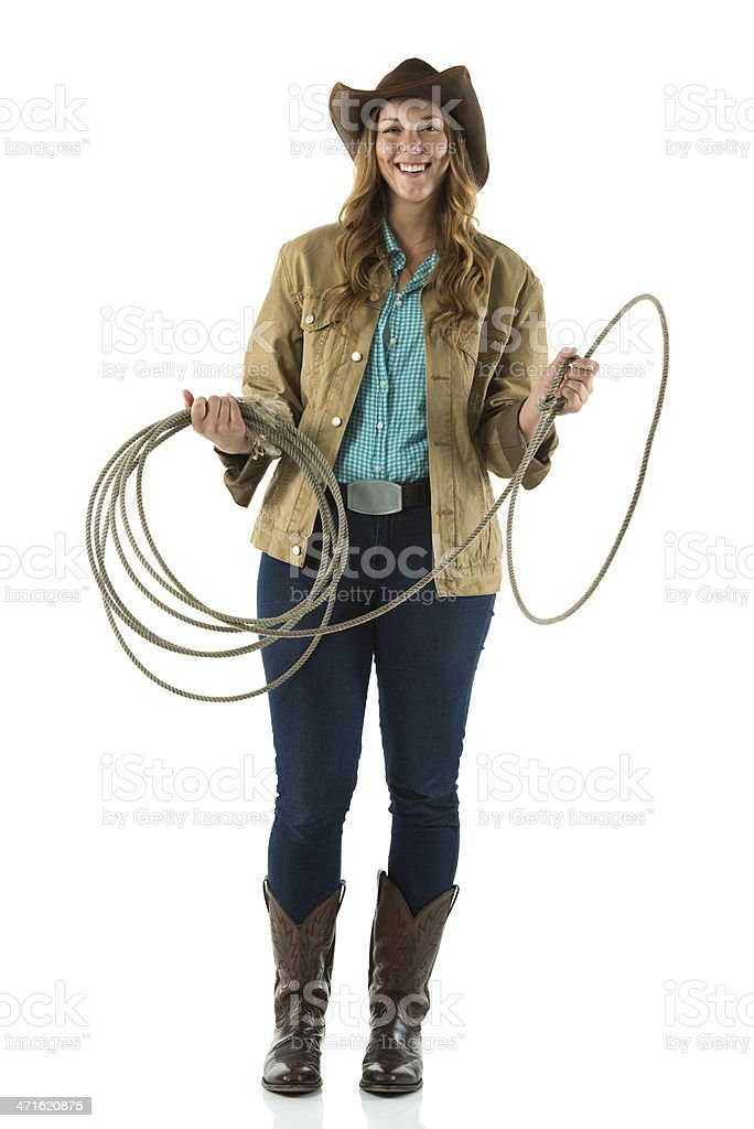 Cowgirl standing with a lasso and smiling royalty-free stock photo