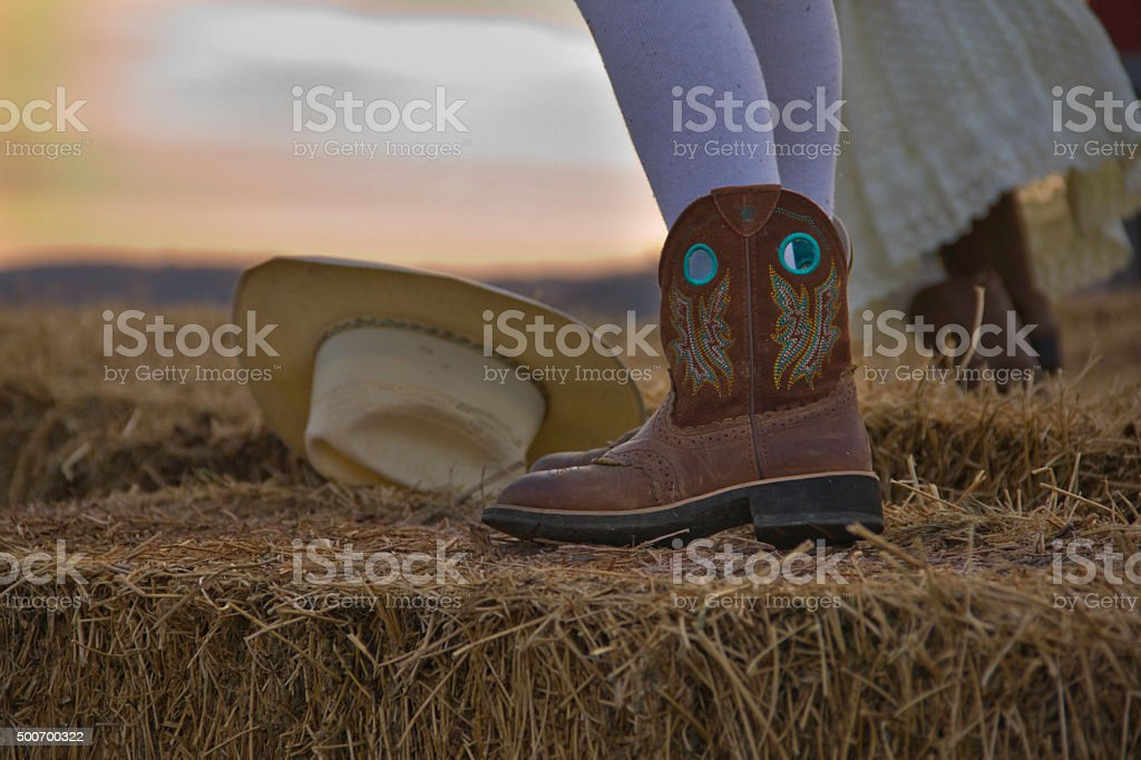 Cowgirl stands on a Hay Bale while Sister Plays stock photo