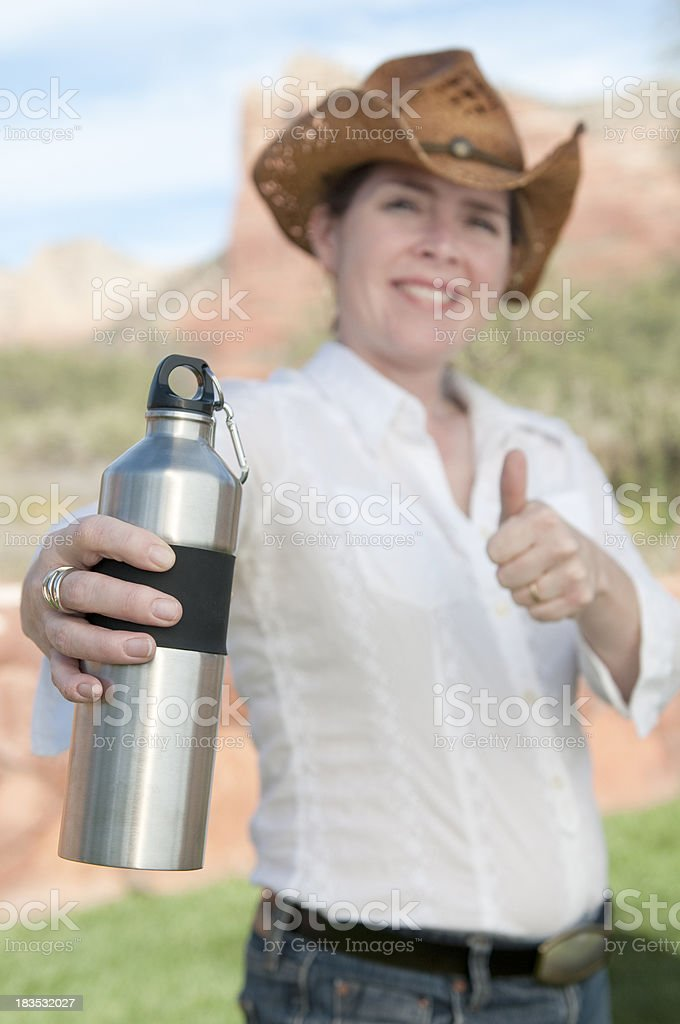 Cowgirl using a stainless steel water bottle royalty-free stock photo