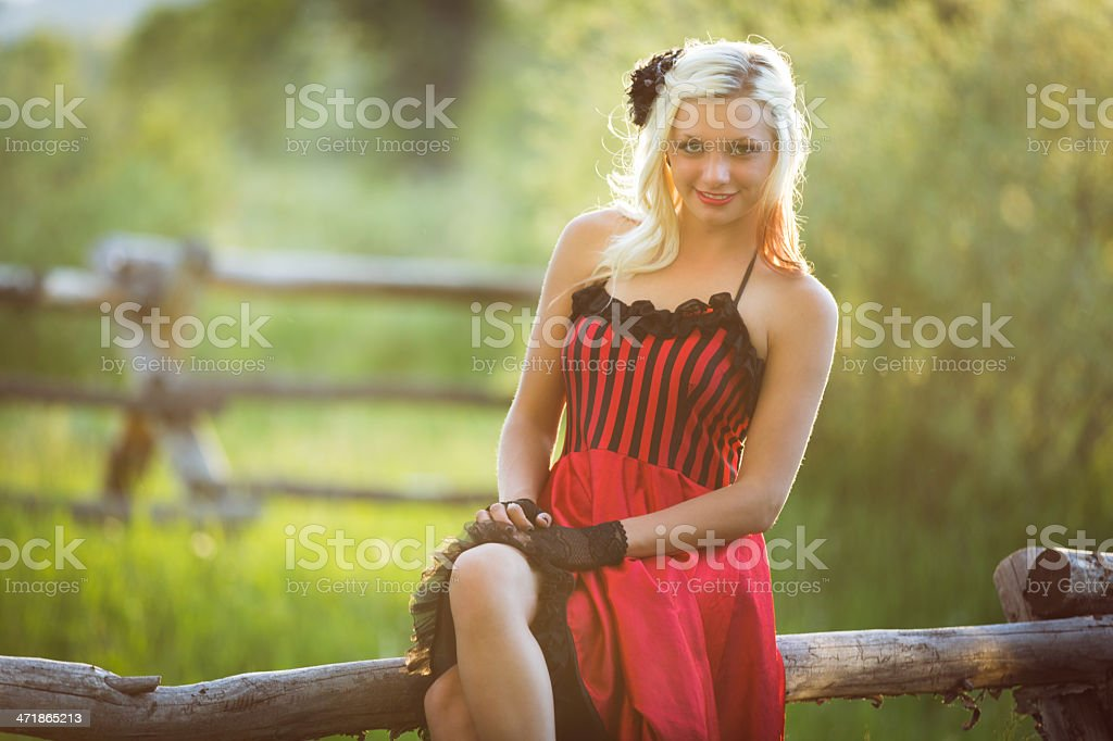 Cowgirl wearing saloon girl outfit at ranch stock photo