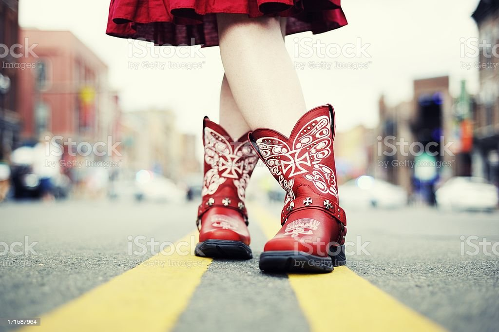 Cowgirl with Red Boots in the Road royalty-free stock photo