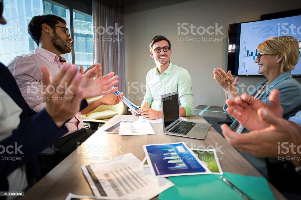 Coworkers applauding a colleague after presentation stock photo