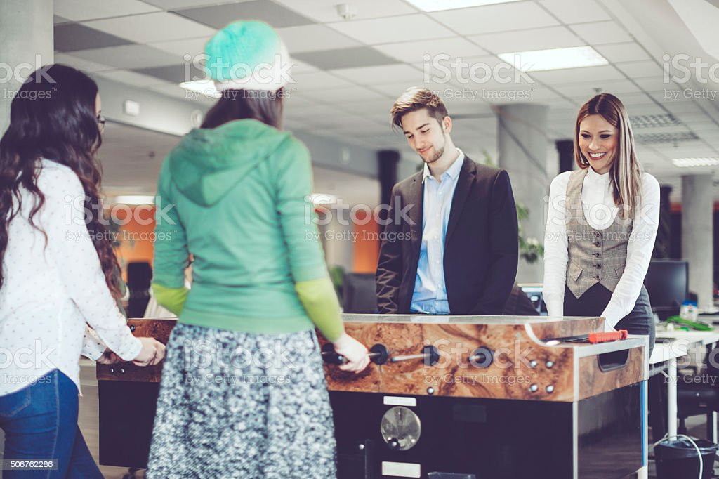 Coworkers are playing foosball at work stock photo