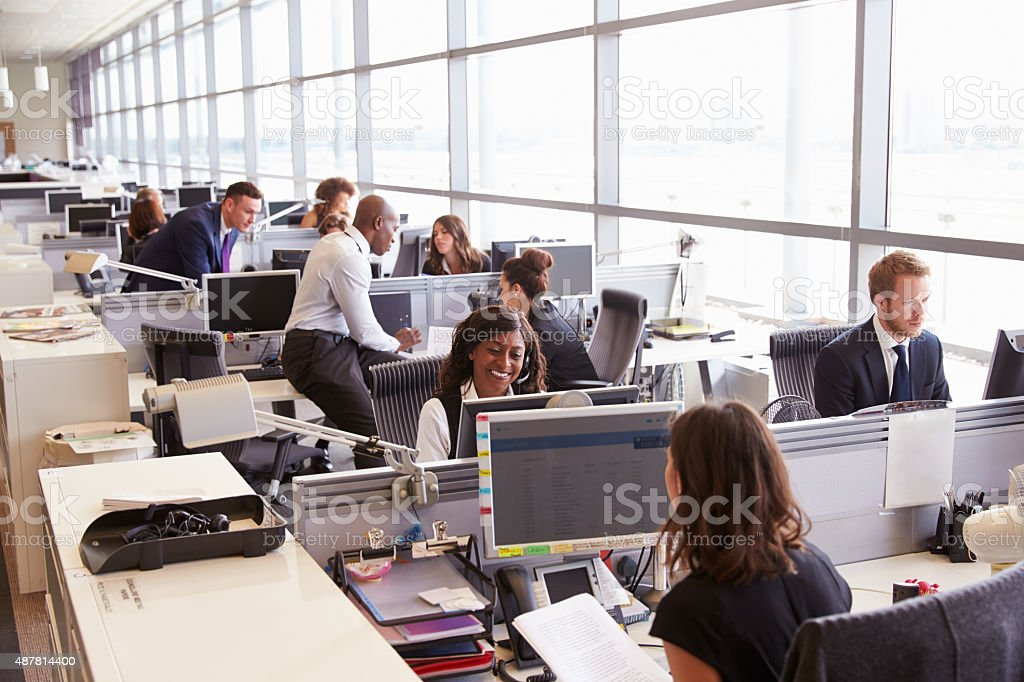Coworkers at their desks in a busy, open plan office stock photo