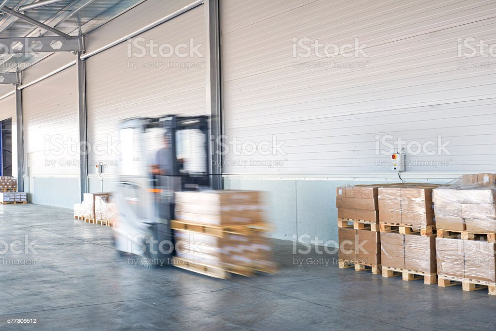 Coworkers carrying wooden boxes in warehouse. stock photo