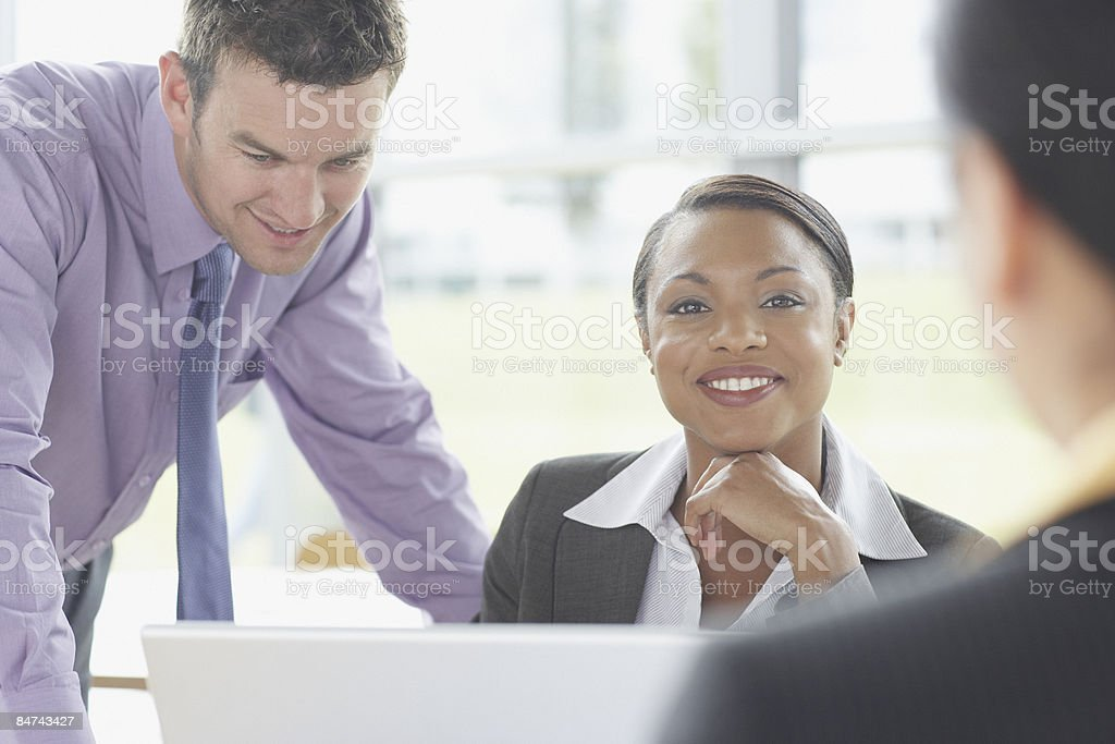 Co-workers gathered around laptop royalty-free stock photo