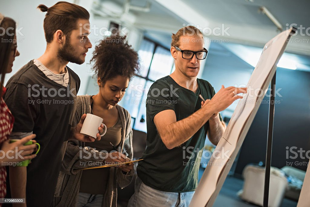 Co-workers having a discussion about something on an easel stock photo