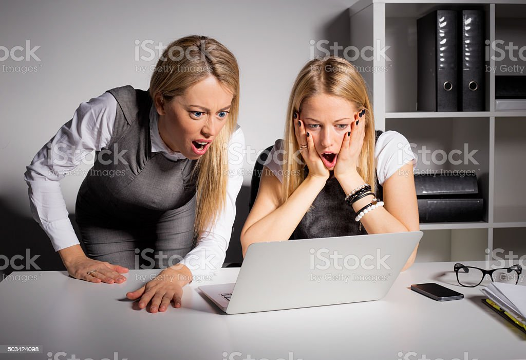 Co-workers looking at computer in shock stock photo