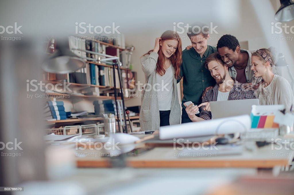 Coworkers looking at mobile phone stock photo