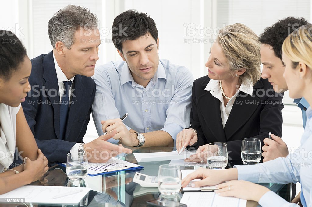 Coworkers meeting around a table stock photo