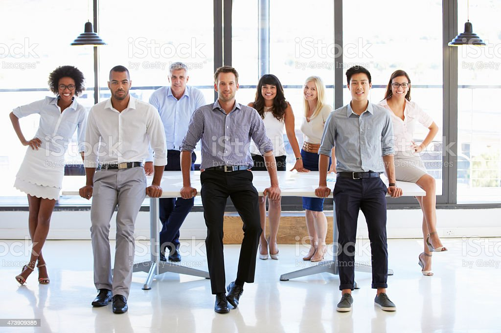 Coworkers posing to camera in meeting room stock photo