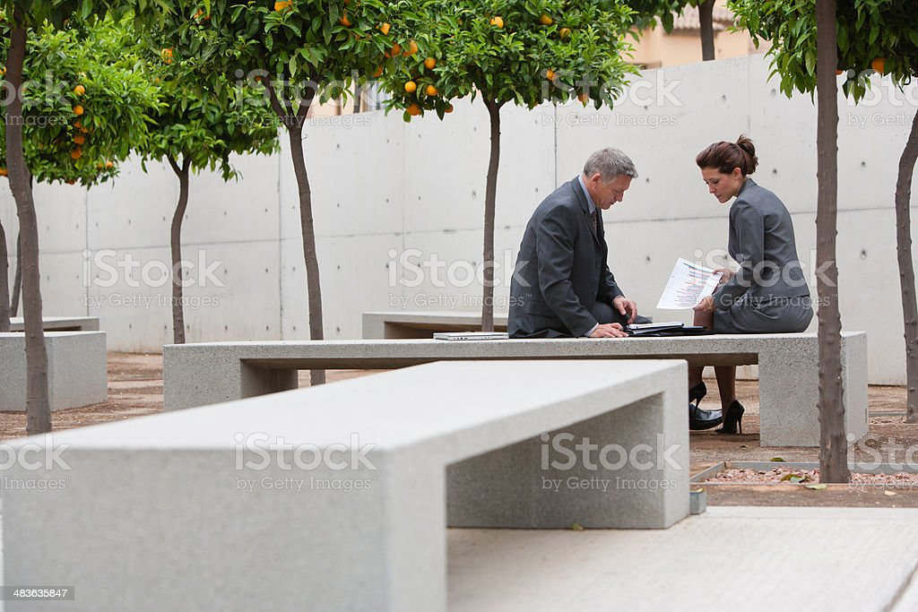 Co-workers talking in office building courtyard stock photo