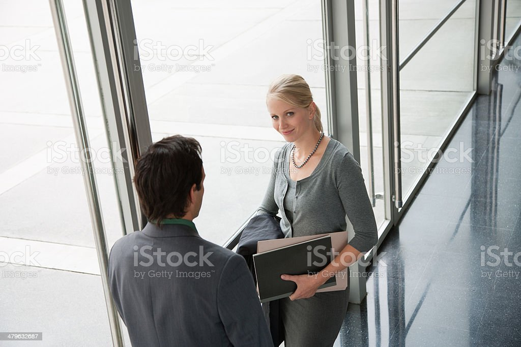 Co-workers talking in office lobby stock photo