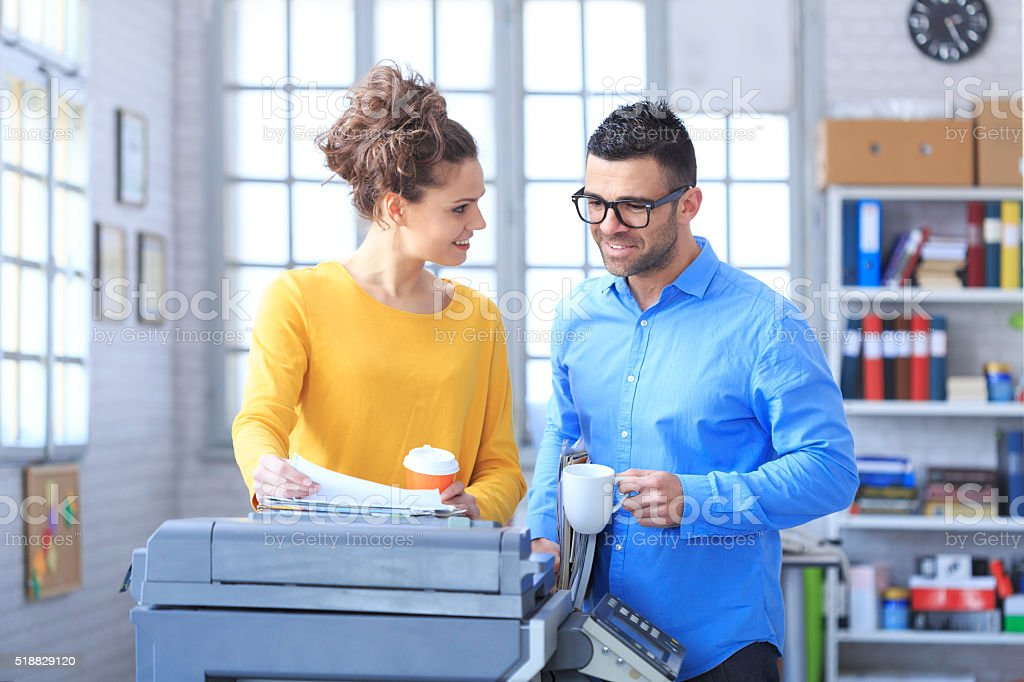 Coworkers working and drinking coffee together at the office stock photo