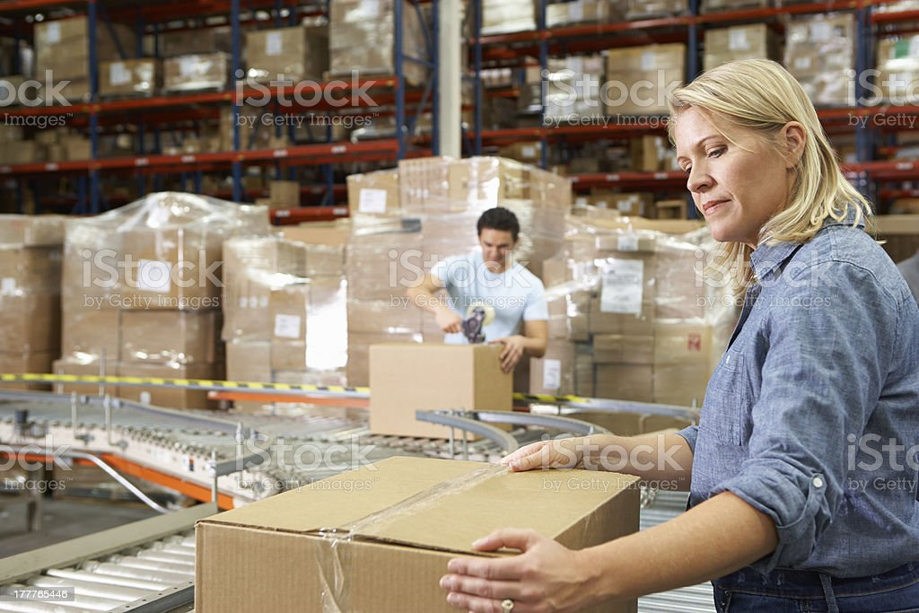 Coworkers workings in a distribution warehouse packing  stock photo
