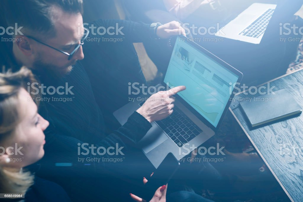 Coworking process in office.Two young colleagues using computer.Woman wearing black pullover and sitting on the sofa.Graphs and diagramm on laptop screen.Horizontal, visual effects. stock photo