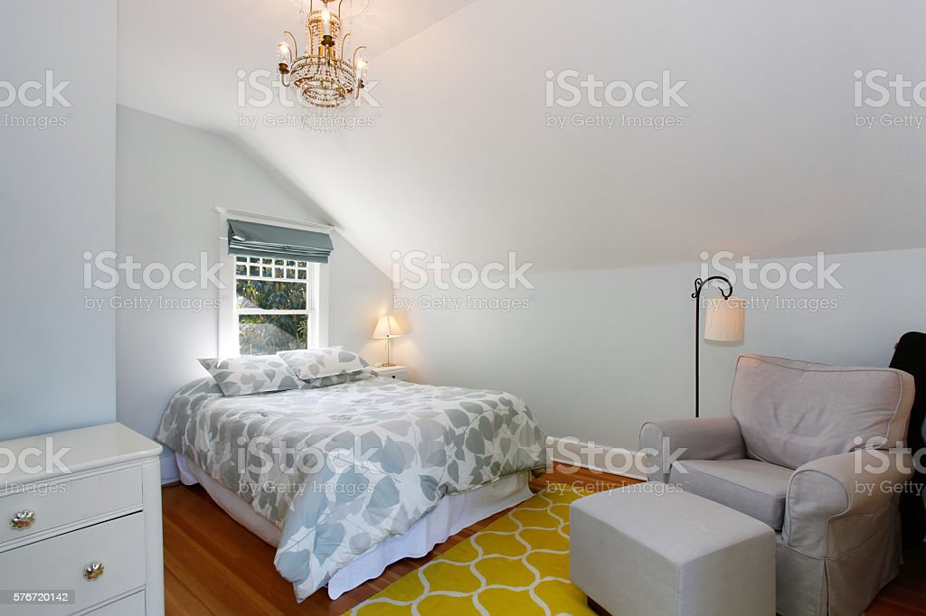 Cozy attic bedroom with white walls and yellow rug. stock photo