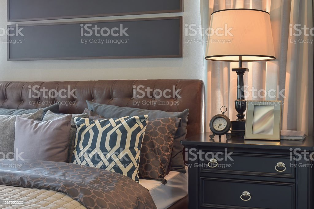 Cozy bedroom interior with pillows and reading lamp stock photo