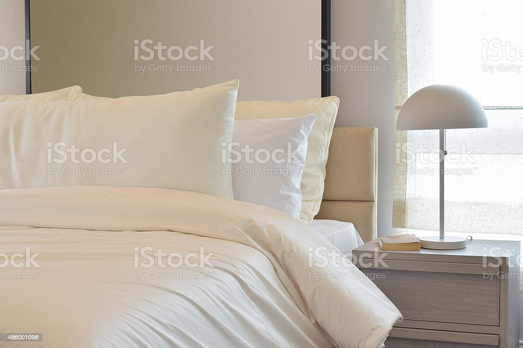 Cozy bedroom with pillows and reading lamp on bedside table stock photo