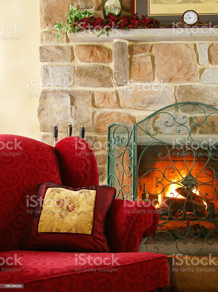 cozy chair by the fire stock photo