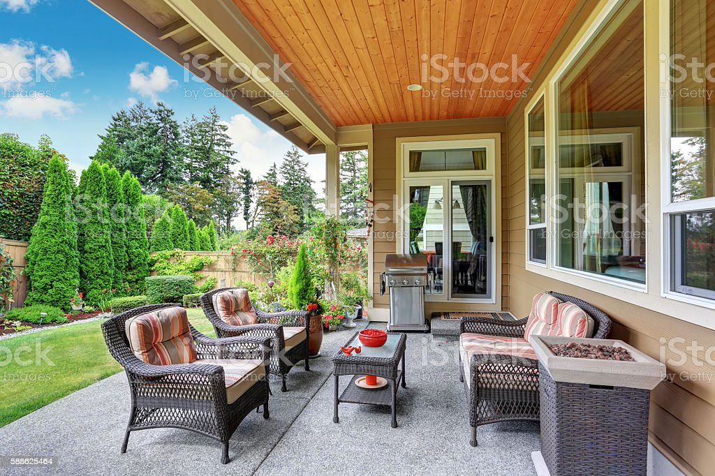 Cozy covered sitting area with wicker chairs and barbecue stock photo