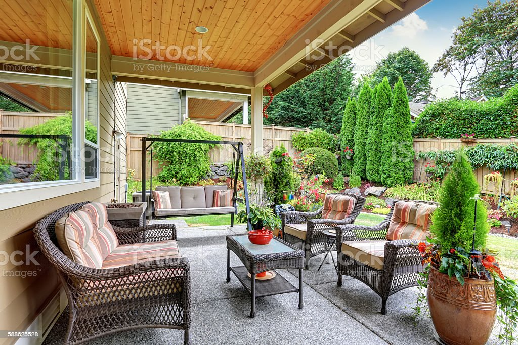 Cozy covered sitting area with wicker chairs and swing stock photo