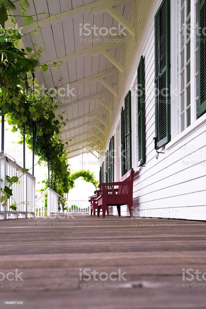 Comoda coperta galleria in legno con uva e panche foto stock royalty-free
