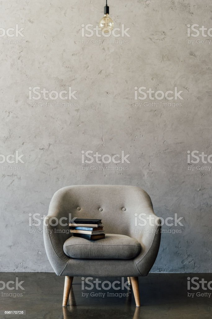 Cozy grey armchair with books and light bulb in empty room stock photo