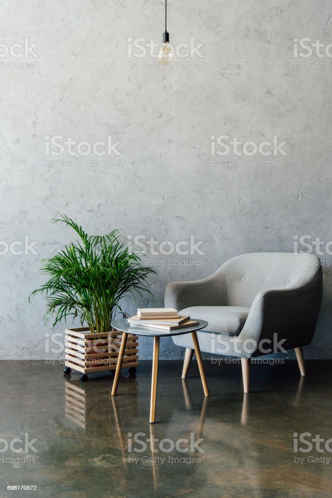 Cozy grey armchair with books on coffee table and green potted plant in empty room stock photo