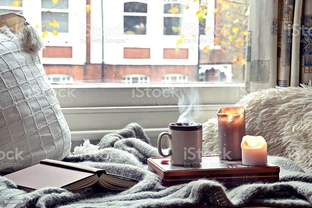 Cozy home. Candles, book and cup of tea stock photo