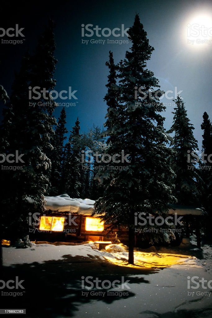 Cozy log cabin at moon-lit winter night royalty-free stock photo