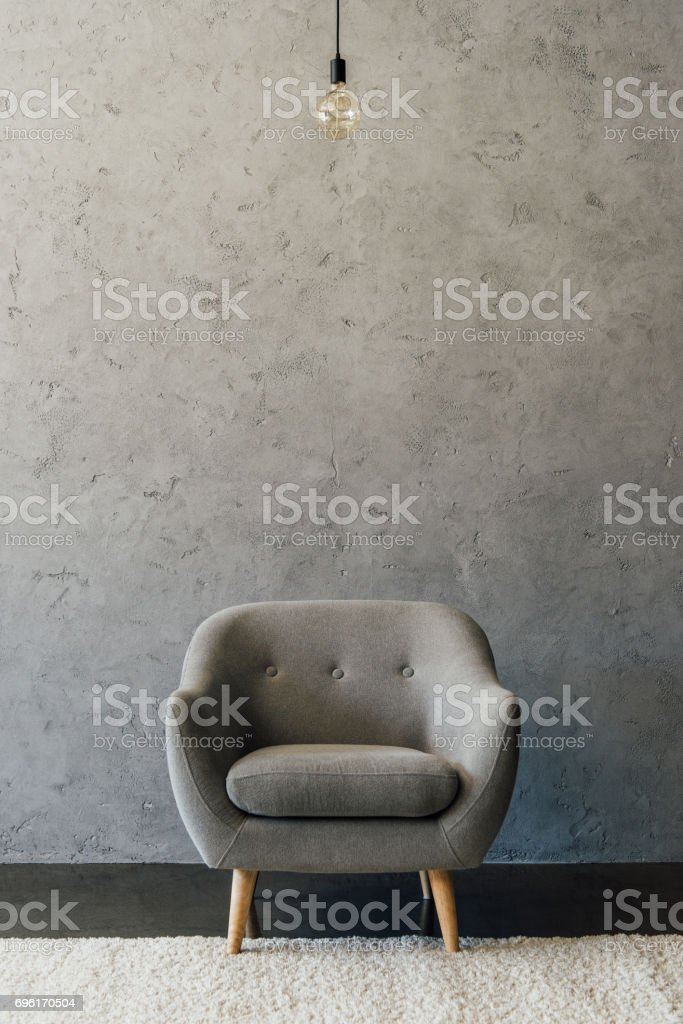 Cozy modern grey armchair and light bulb hanging in empty room stock photo