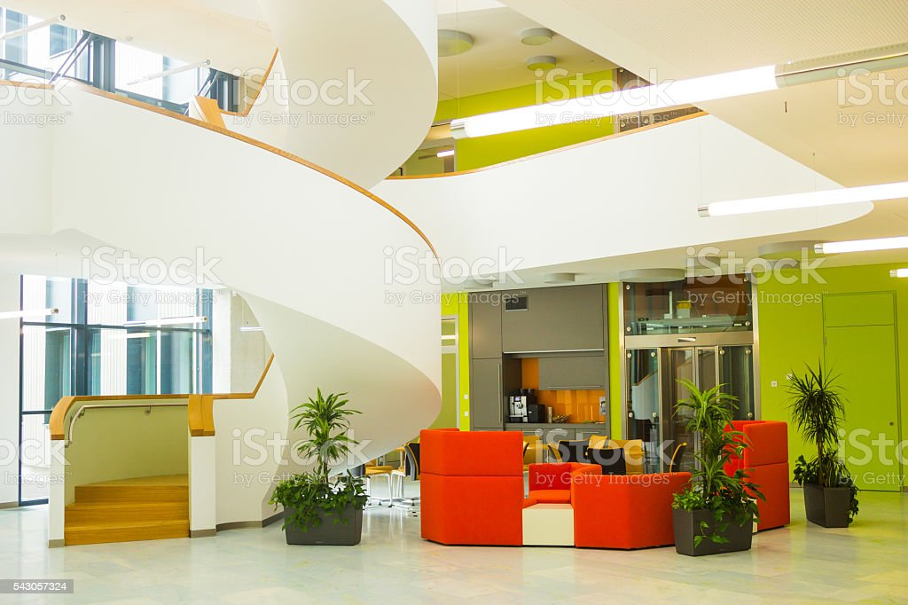 Cozy modern style cafe with red sofas near spiral stairs stock photo