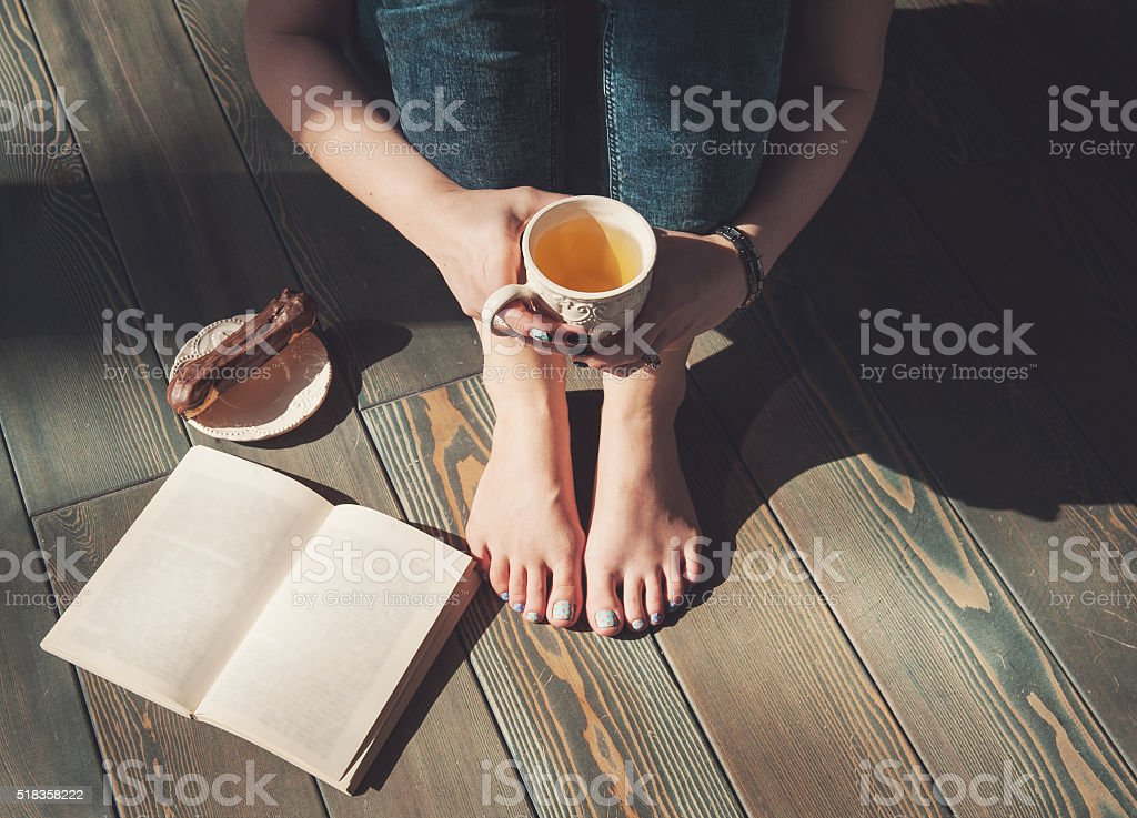 Cozy photo of young woman with tea and book stock photo