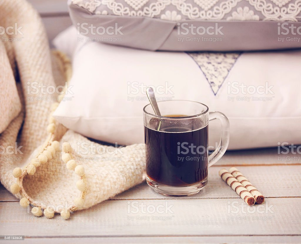 Cozy still life with coffee, pillows and plaid stock photo