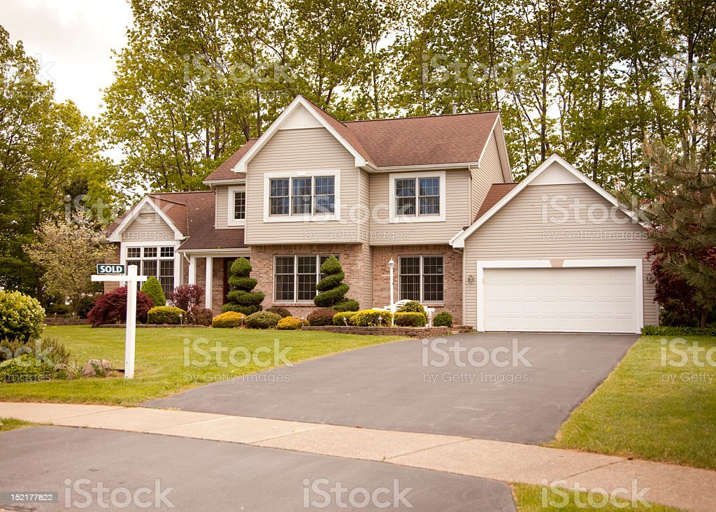 Cozy two-floor house with garage being sold stock photo