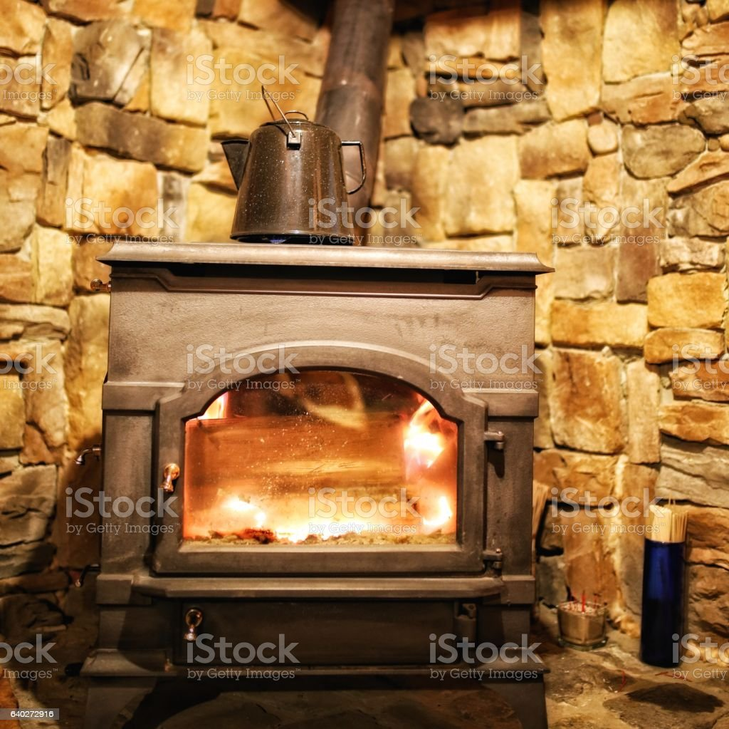 Cozy Wood Burning Fireplace Stove, Matches, Water Kettle, Log Cabin stock photo